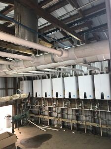 Installation of sixteen Navien NPE-240S Tankless Water Heaters.